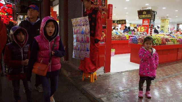 Children walk past by a man dressed like an emperor, center, promoting photography services in Beijing on Thursday. The official Xinhua News Agency says China's ruling Communist Party has decided to abolish the country's one-child policy and allow all couples to have two children. (AP Photo/Ng Han Guan)